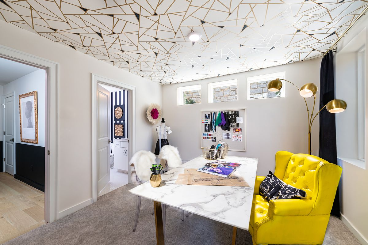 Bedroom outfitted with table, bright yellow chair and ceiling decorated with graphics.