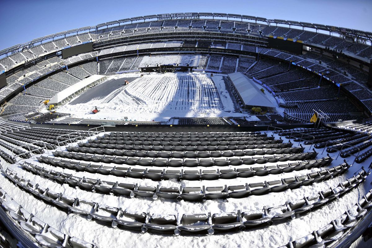 A general view as stadium workers clean snow from the field and stands at MetLife Stadium on Wednesday