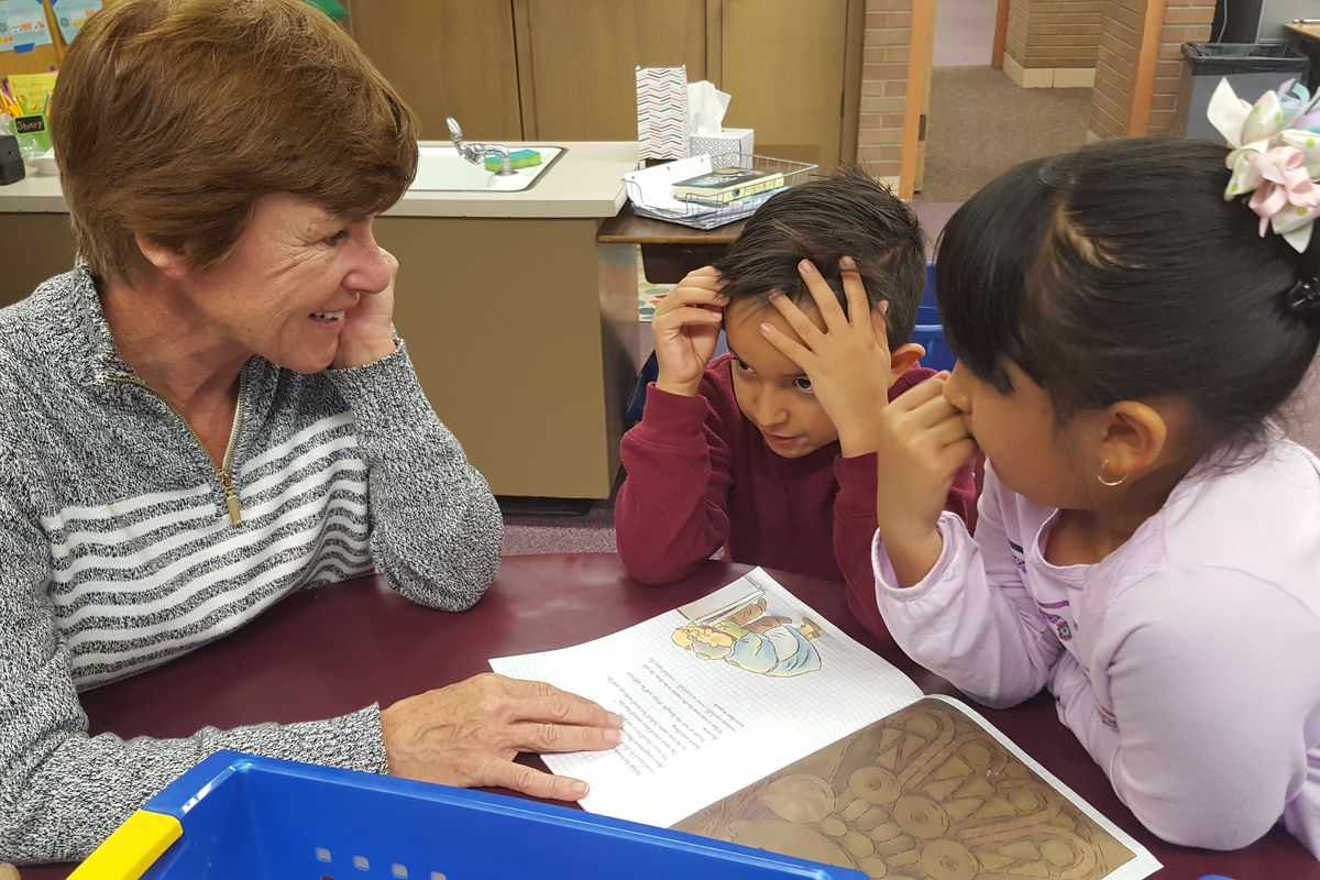 Volunteer Cindy Stechmeyer reads with two second graders during reading club at Lumberg Elementary in Edgewater.