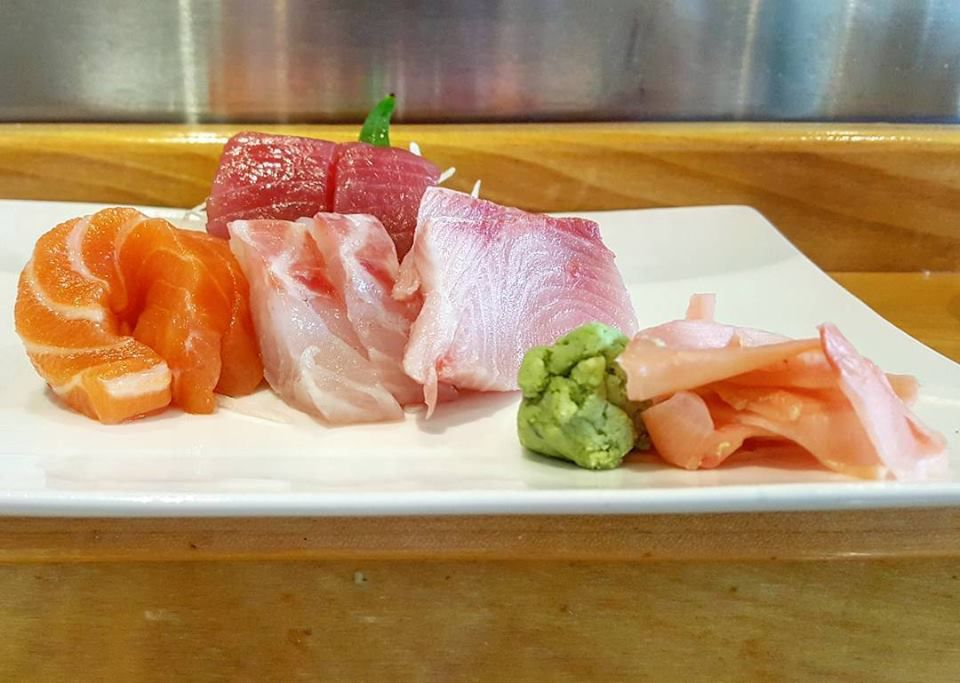 Several pieces of sashimi sit on a white plate on a wooden counter