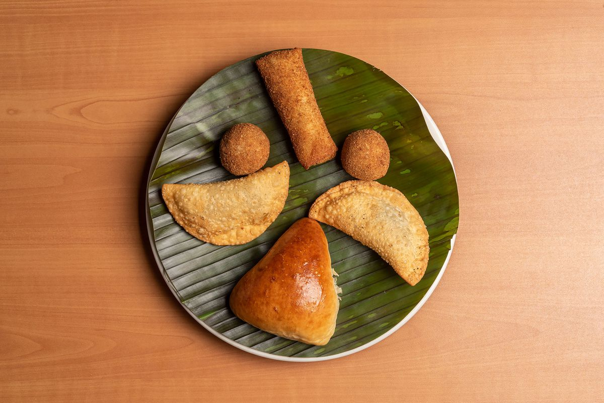 Sri Lankan snacks such as buttery fish buns and patties on a banana leaf.
