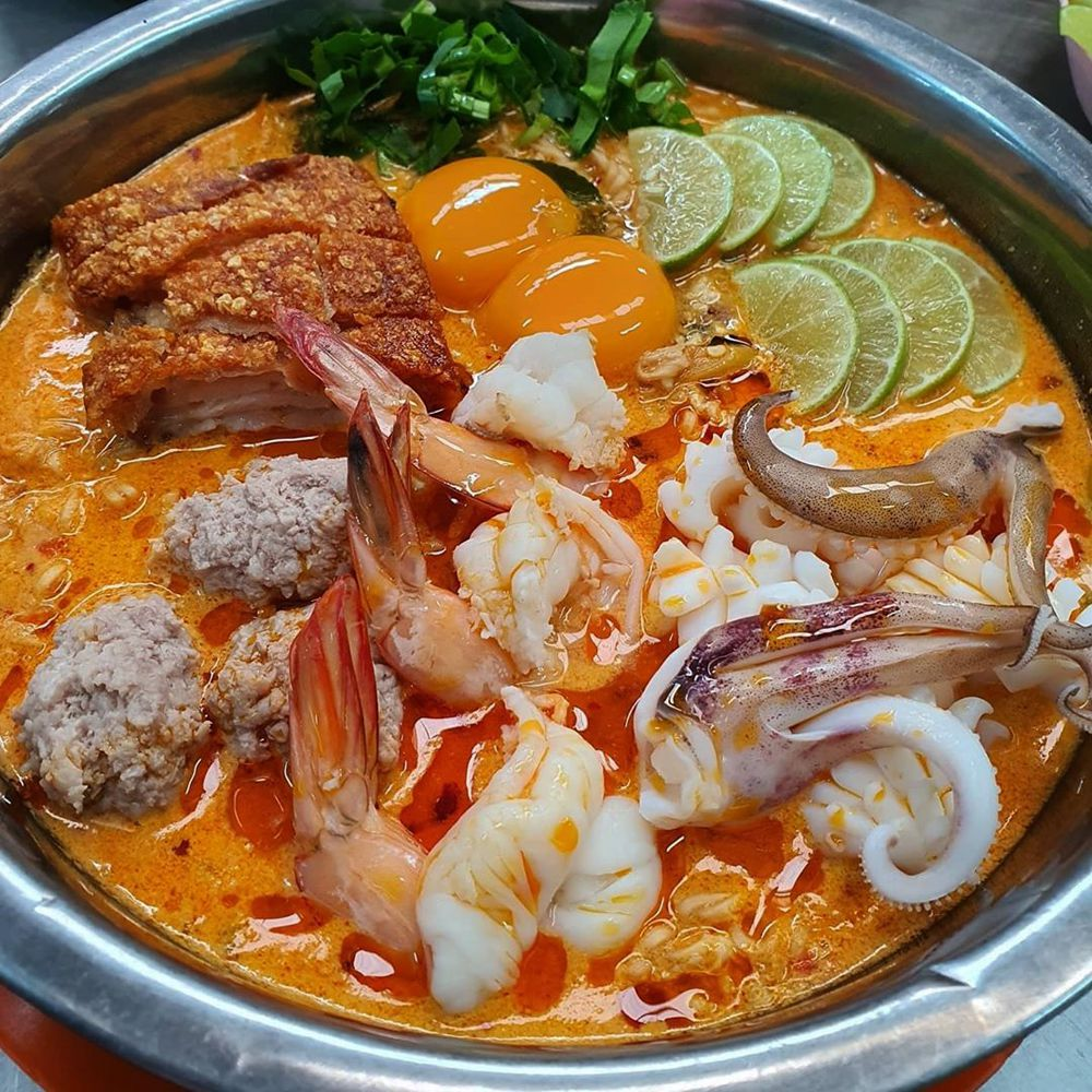 A soup with an orange base and shrimp, chicken katsu, and other meats