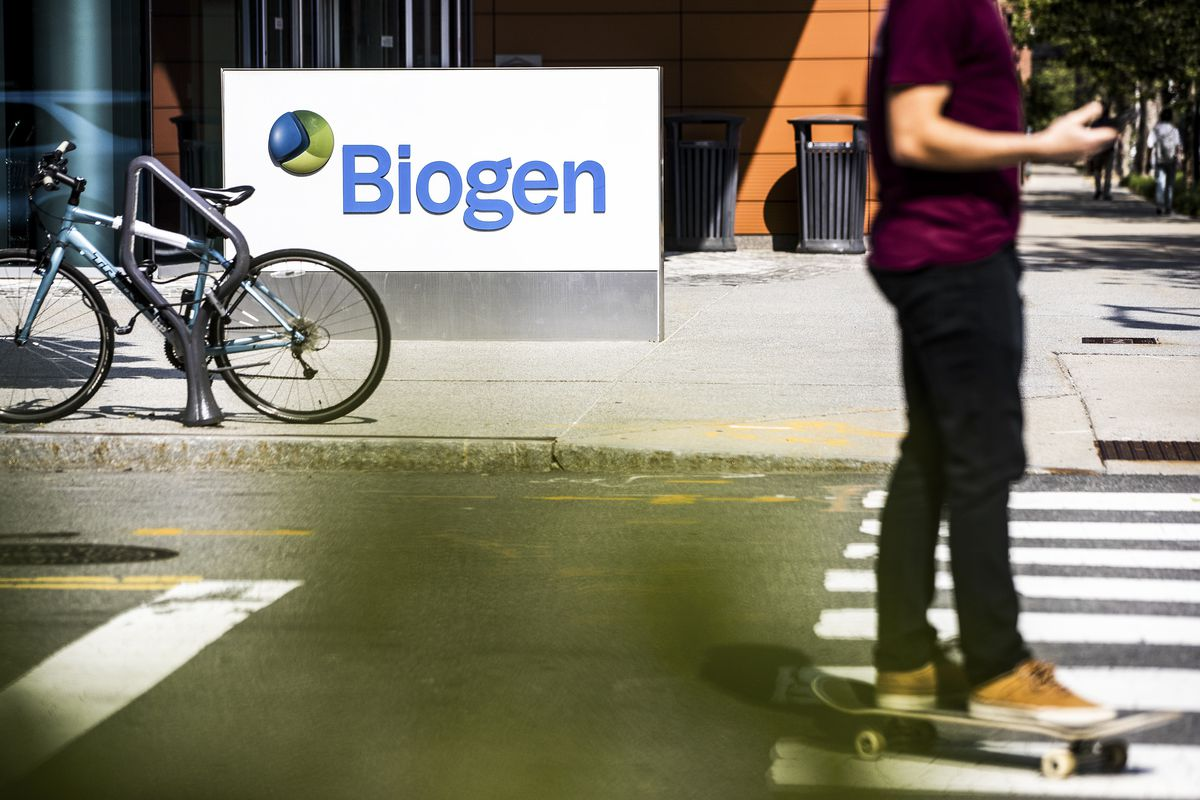 """A person on a skateboard goes past a sign that reads """"Biogen"""" outside the company's headquarters."""