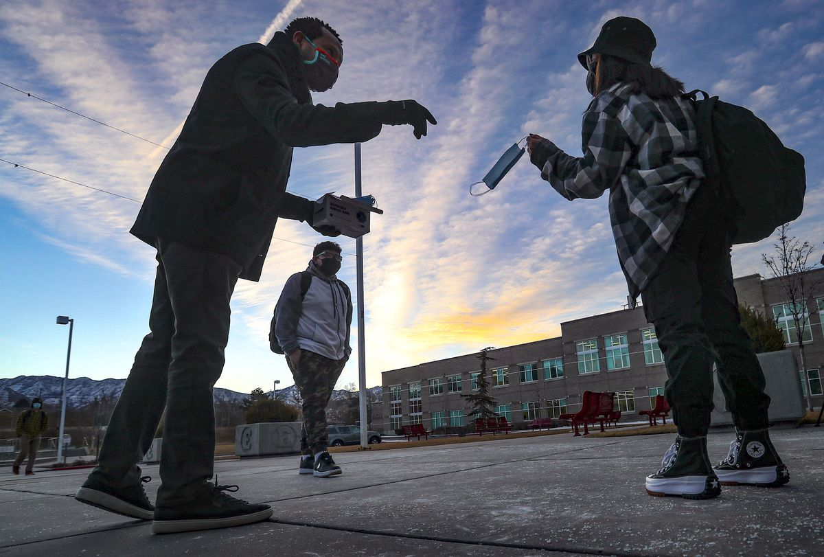 Salt Lake City School District board member Mohamed Baayd, right, greets students and hands out masks as they arrive at East High School in Salt Lake City for their first day of in-person learning in almost a year on Monday, Feb. 8, 2021.