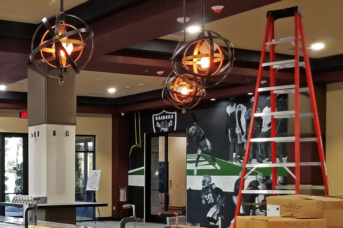 A bar with a Las Vegas Raiders mural, a ladder, and three spherical lights