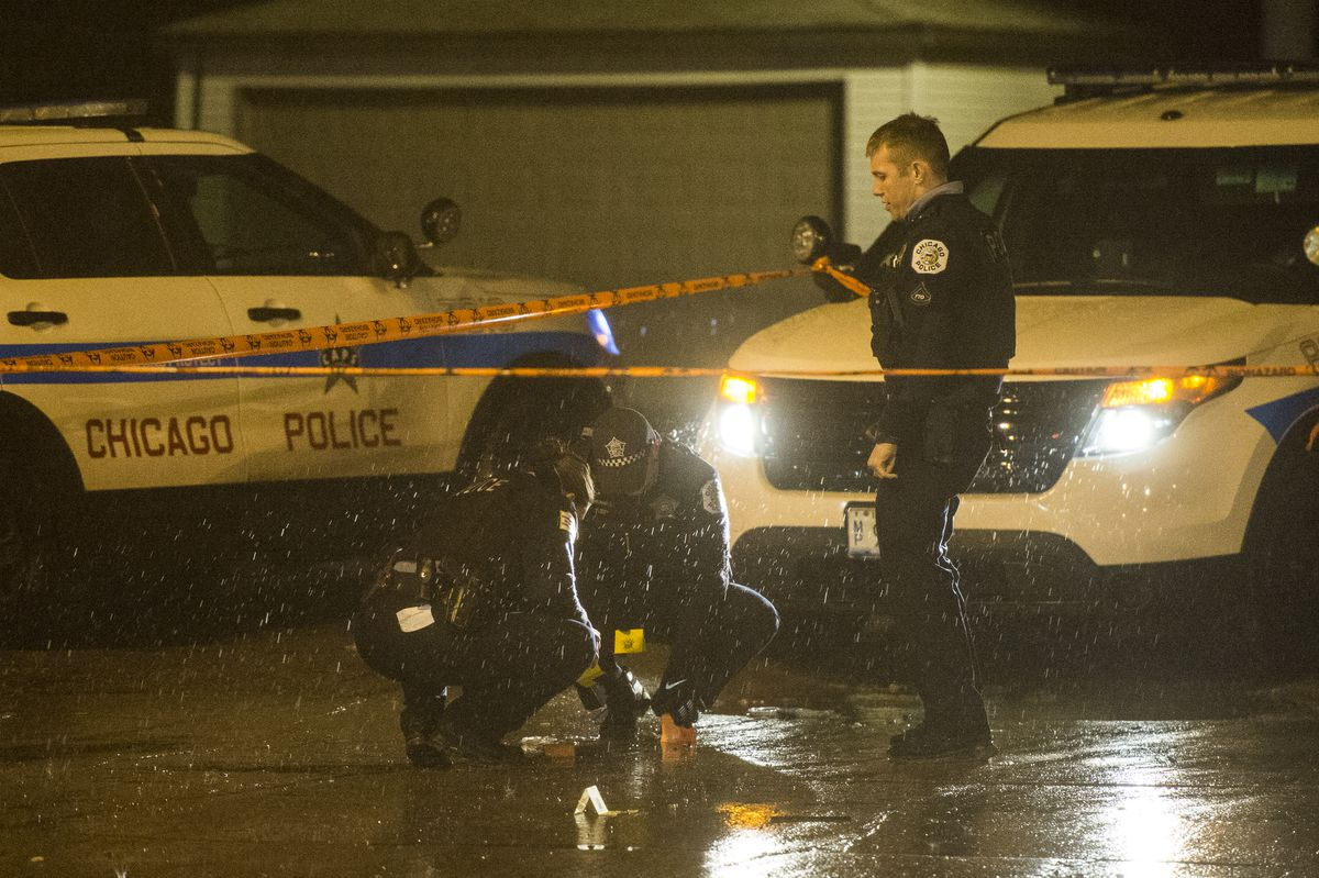 Police place evidence markers at the scene of a shooting early Tuesday in Lawndale.   Tyler LaRiviere/Sun-Times