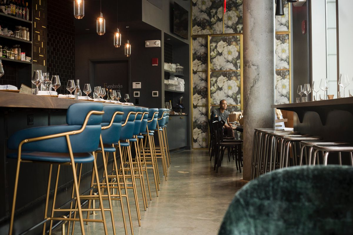 Blue and gold bar stools line a dark brown bar, with backless silver stools arranged at a window counter