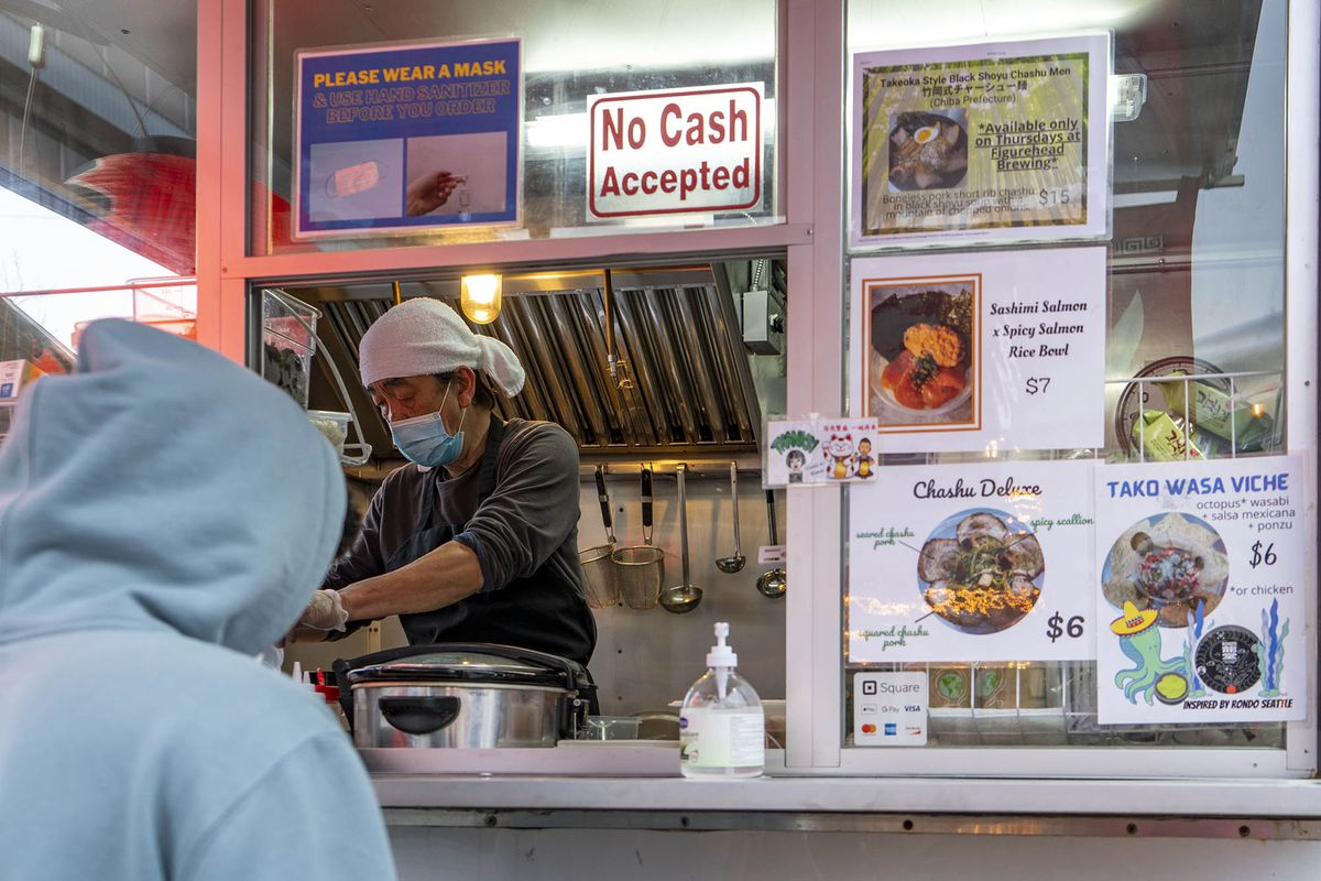 """A masked chef serves ramen from a small window to a customer wearing a light blue hoodie; the menu is displayed to the right and there's a sign that says """"no cash accepted."""""""