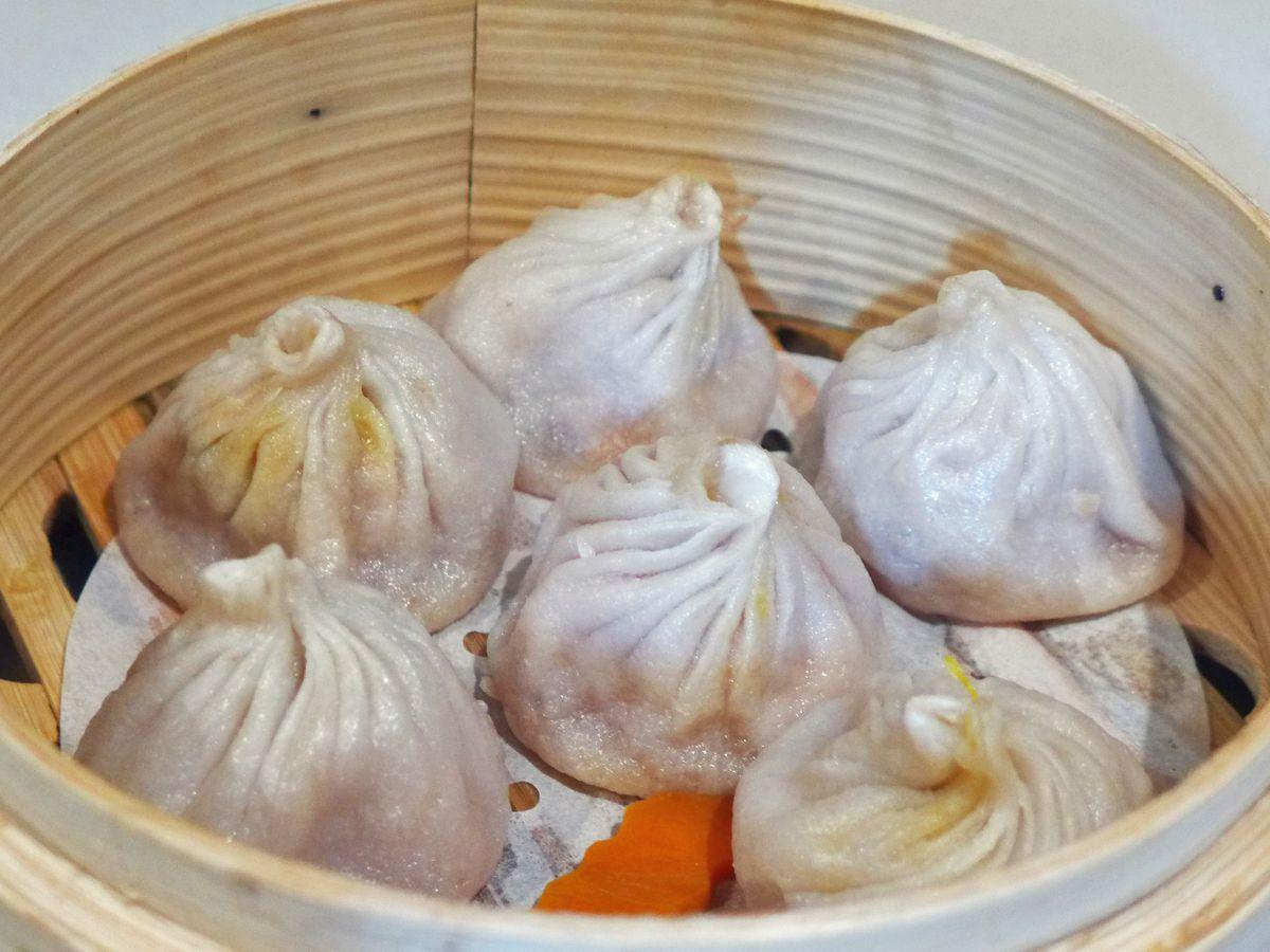 A basket steamer with six puckered dumplings.