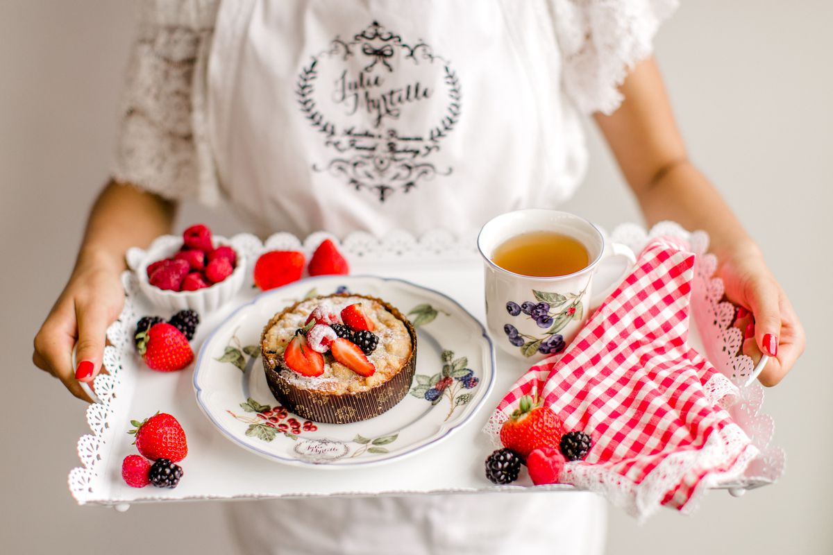 A person holding a tray with a berry-covered tart, scattered berries, a mug of tea, and a red-and-white patterned napkin