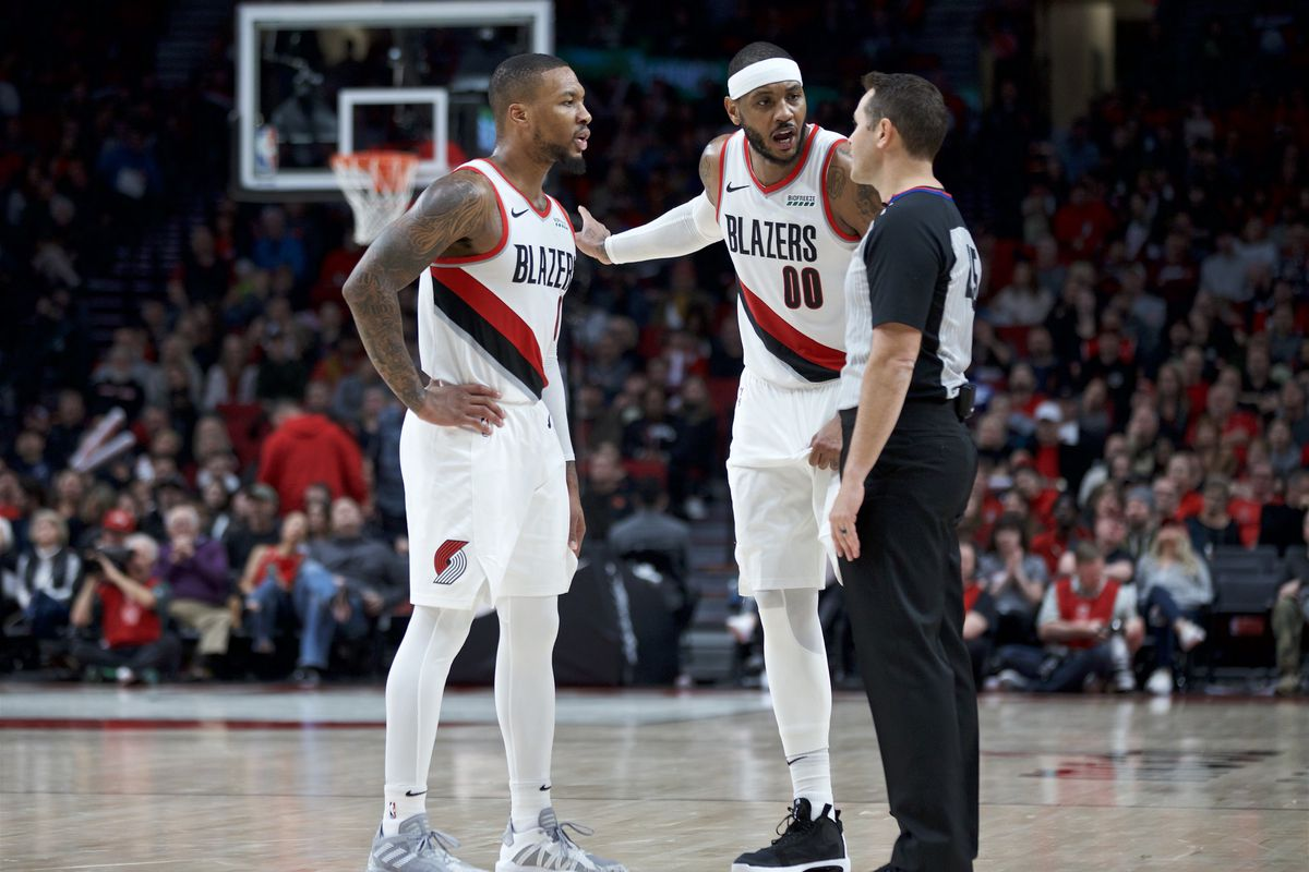 Portland Trail Blazers forward Carmelo Anthony and guard Damian Lillard  talk to referee Brian Forte during the third quarter at the Moda Center.