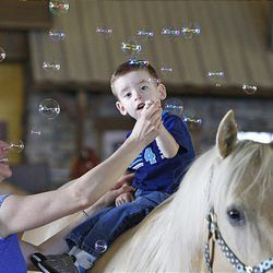 Ben Kubuoyn sits on a horse as his mother, Nikki Kubuoyn, holds him and Andrea Smith blows bubbles over them at the Buffalo Ranch in Farmington on Thursday as part of a therapeutic riding program.