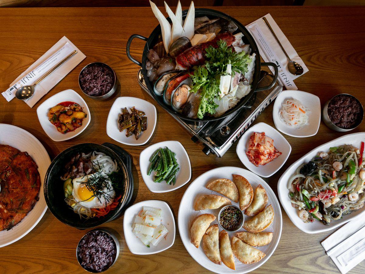 A bunch of plates featuring pots of beautifully arranged seafood, scallion pancake, bibimbap, kimchi, Korean dumplings, and more.