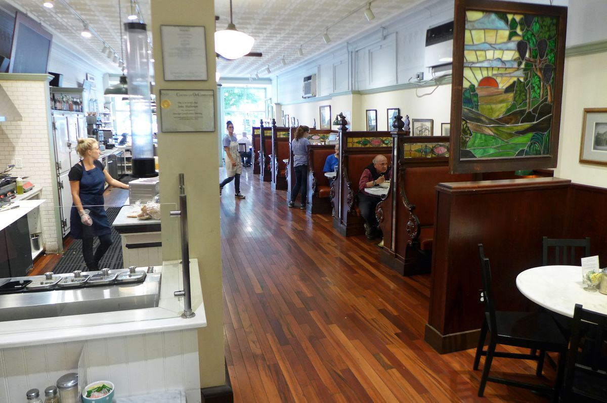 On the right side of the dining room, a row of wooden booths with stained glass embedded in the wood, on the left a woman standing in a sandwich prep area glassed in...