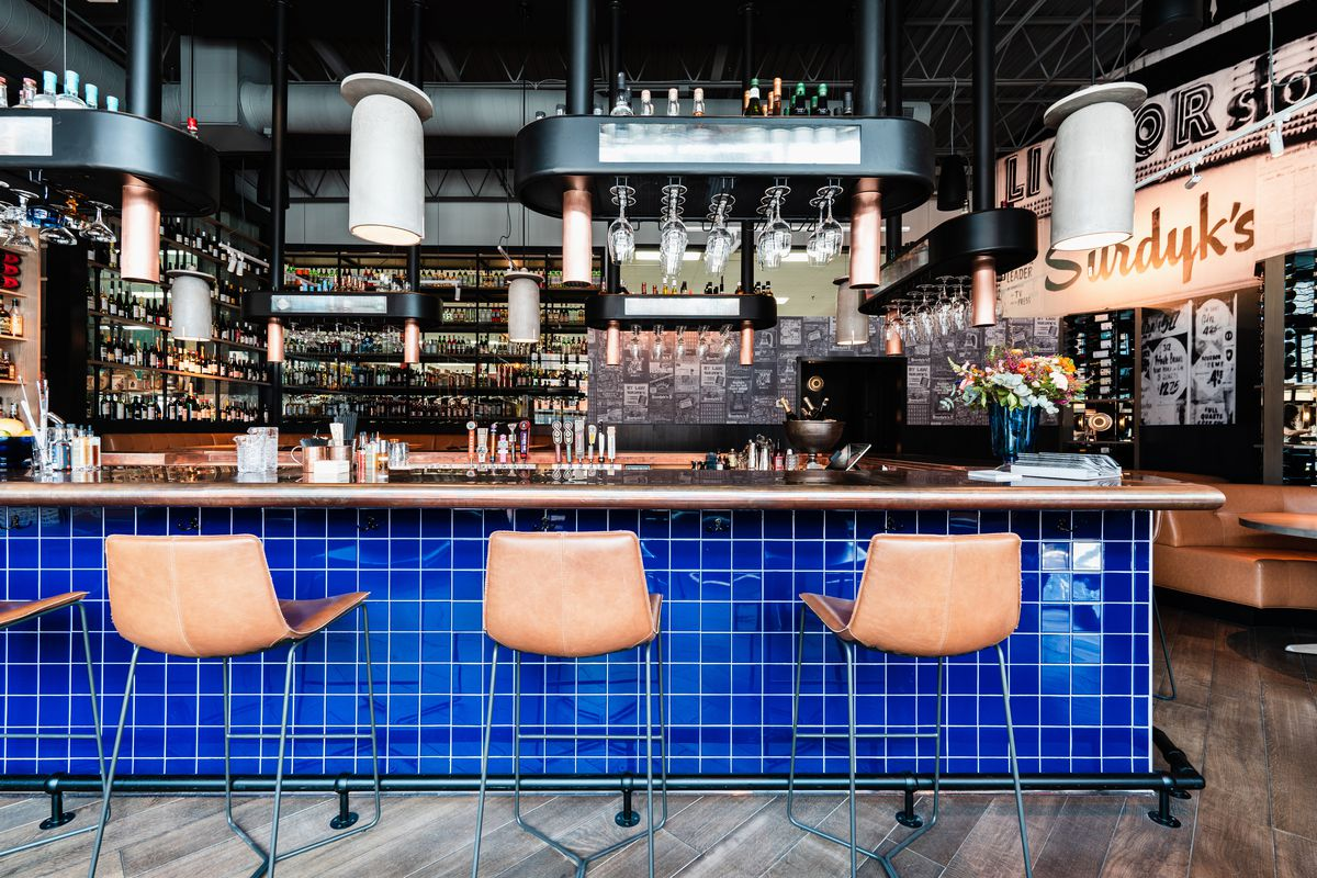"""A cobalt blue tile under a copper bar is flanked by leather bar seats. Black fixtures suspended from the ceiling hold glasses. Visible in the back is a cognac colored big booth with vintage lettering spelling out """"Surdyk's."""" On the very far back wall is floor to ceiling. shelving for wine and liquor bottles."""