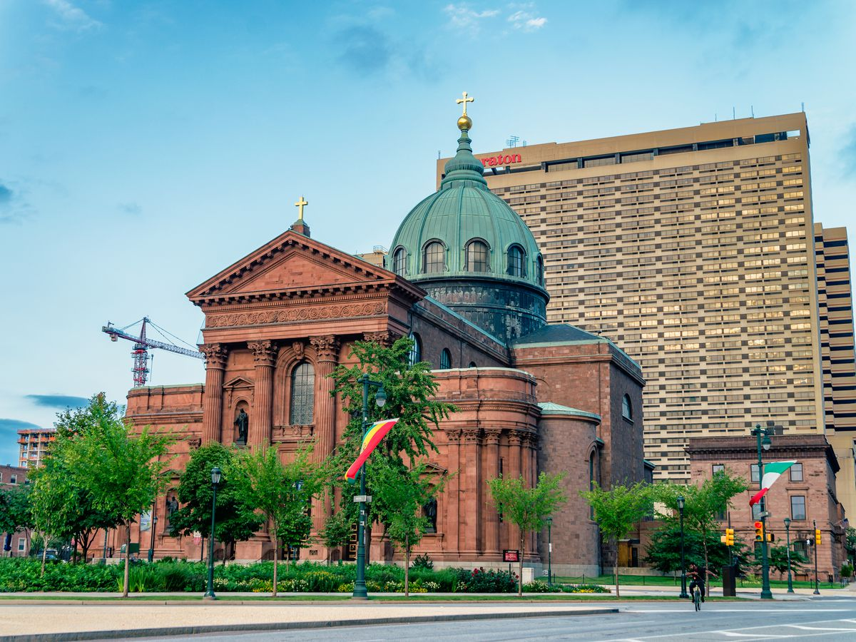 The exterior of the Cathedral Basilica of Saints Peter and Paul in Philadelphia. The facade is red with a green domed tower.