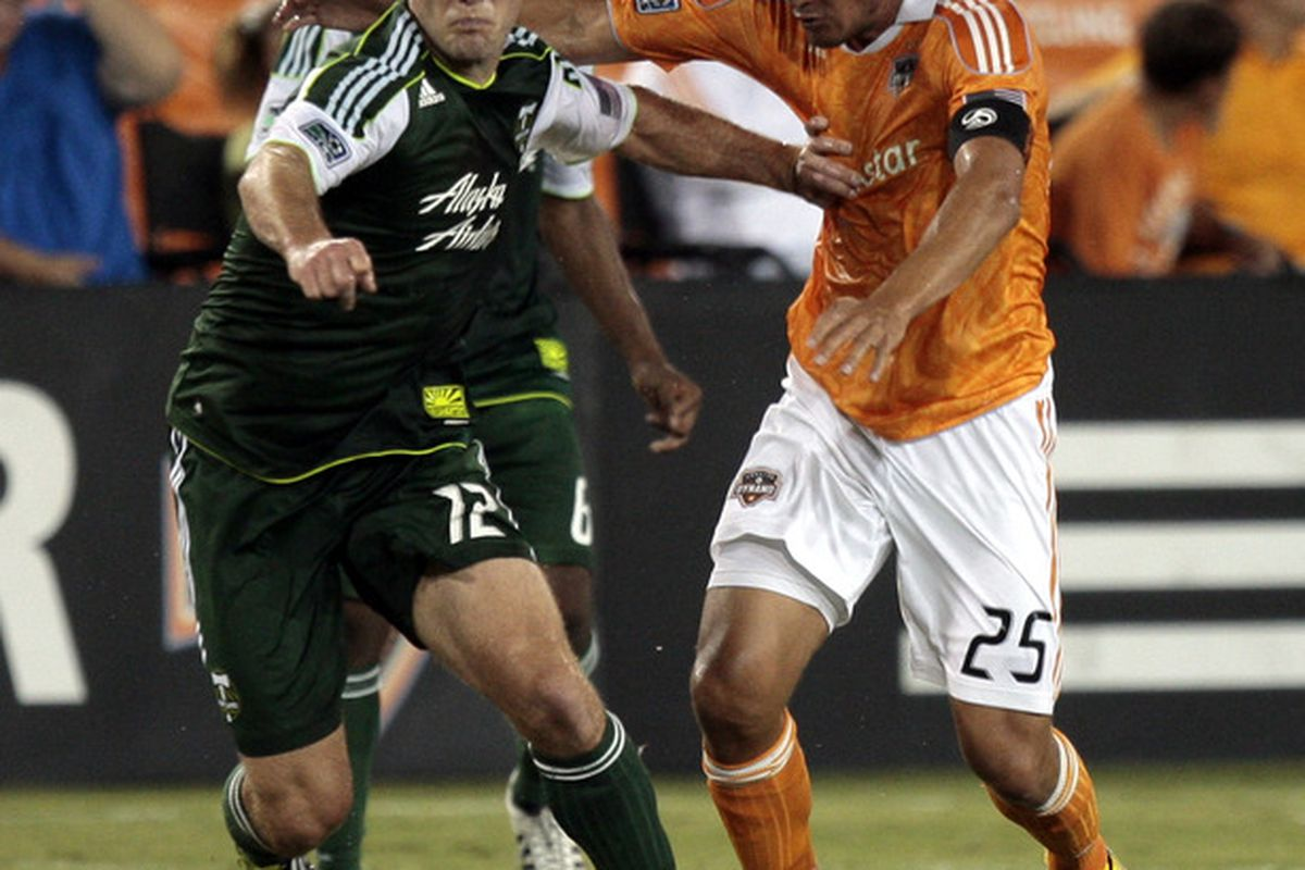HOUSTON - AUGUST 14:  Defender David Horst #12 of the Portland Timbers pushes off forward Brian Ching #25 of the Houston Dynamo in the first half at Robertson Stadium on August 14, 2011 in Houston, Texas.  (Photo by Bob Levey/Getty Images)