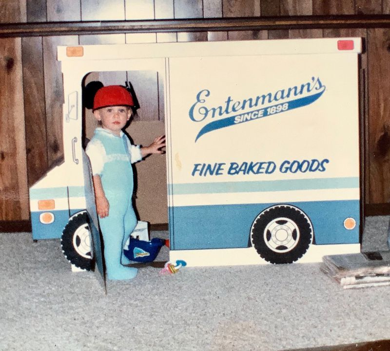 Photo from the 80s showing a toddler wearing a jumpsuit and Mickey Mouse ears hat, standing inside a cardboard cutout of an Entenmann's food truck.