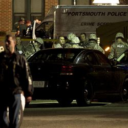 Heavily armed police gather before boarding an armored truck in Greenland, N.H. Thursday April 12, 2012, to go to the site where a man is barricaded in a house after he shot and killed Greenland Police Chief Michael Maloney and wounded four other officers. The police were conducting a drug investigation when the shootings occurred.