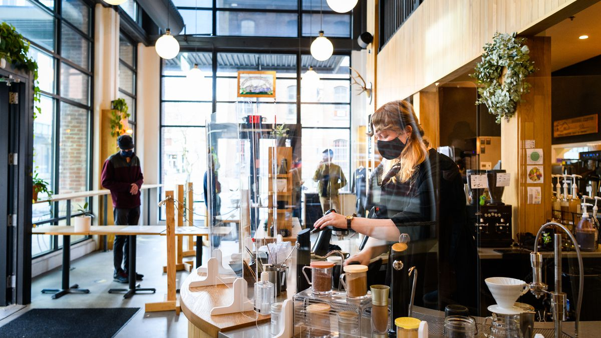A woman in blonde braids and a black mask makes coffee drinks behind the curved bar at Sisters, which has high ceilings and globe lights.