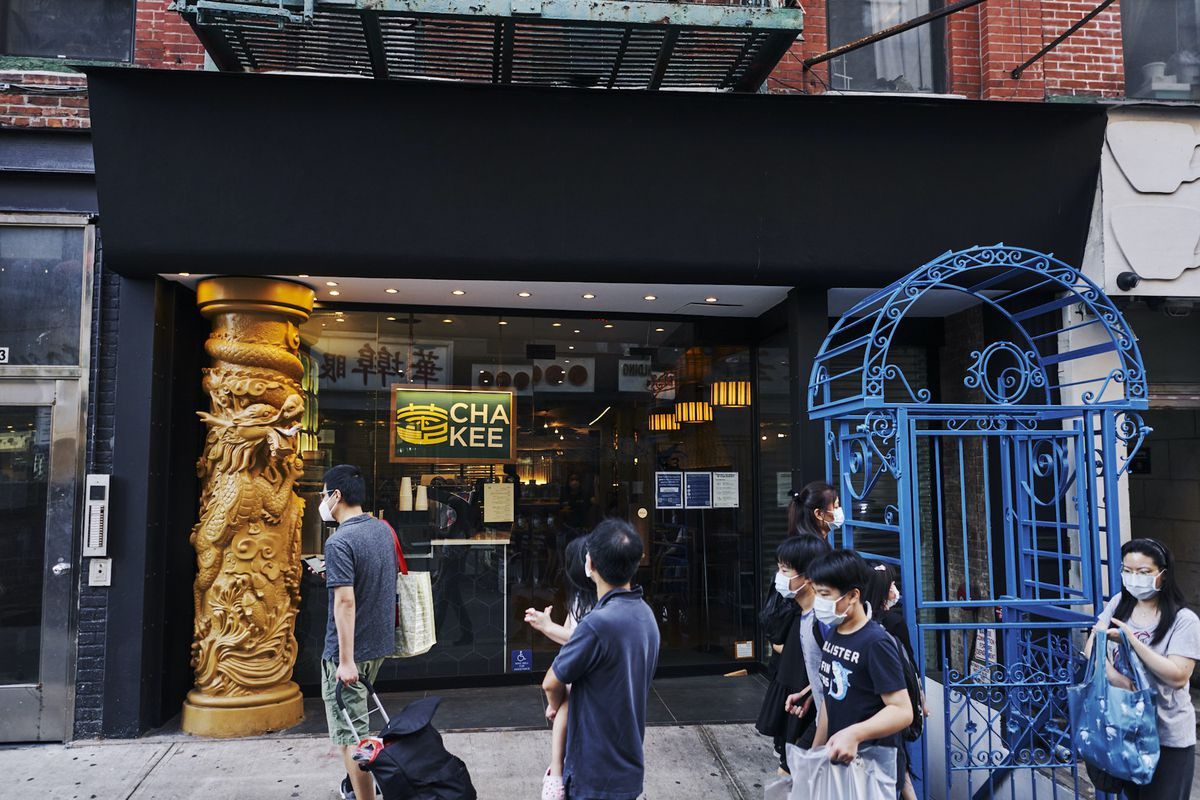 A restaurant entrance with glass windows and a golden column with pedestrians passing by.