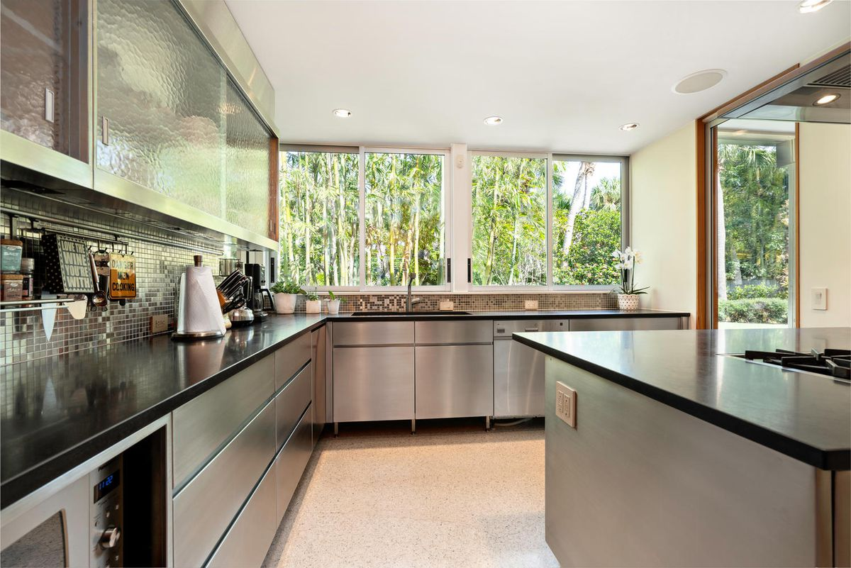 A black and stainless steel kitchen has large windows that look outside.