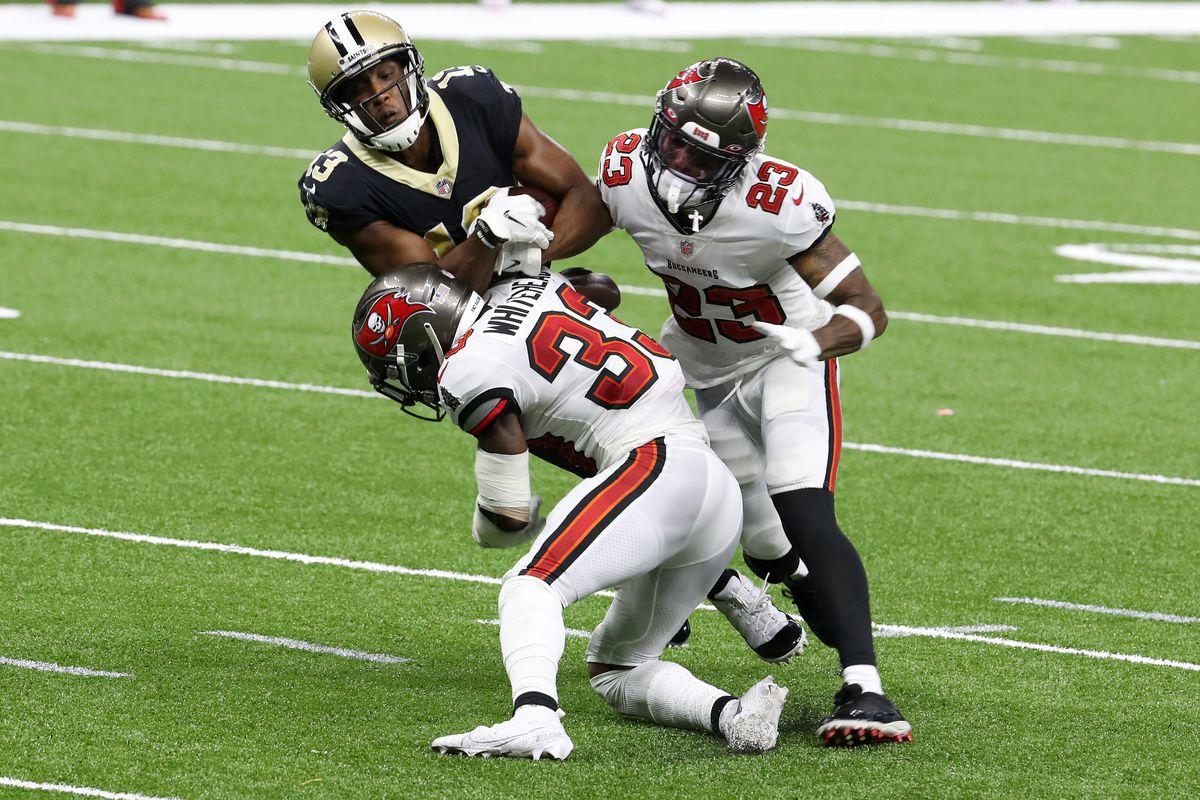 Michael Thomas of the New Orleans Saints is tackled by Jordan Whitehead and Sean Murphy-Bunting of the Tampa Bay Buccaneers during the second quarter at the Mercedes-Benz Superdome on September 13, 2020 in New Orleans, Louisiana.