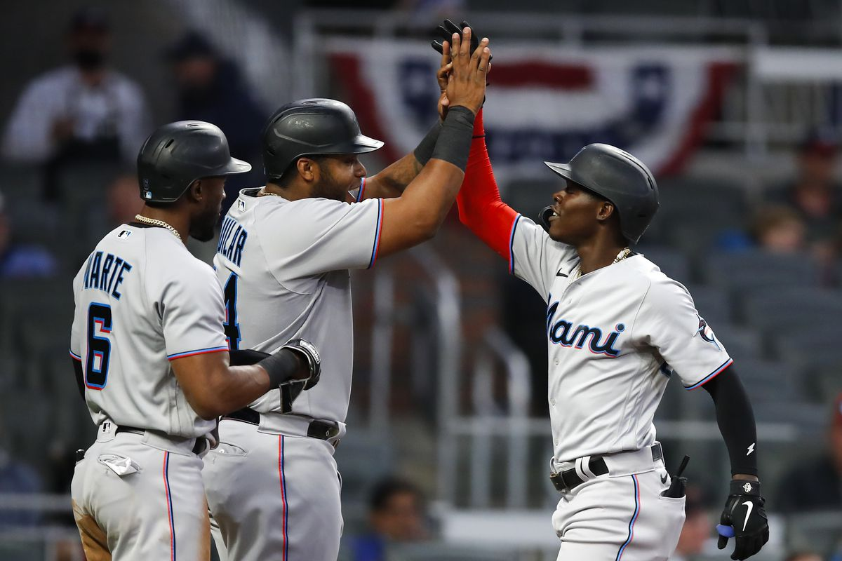 Jazz Chisholm Jr. #2 of the Miami Marlins reacts with Starling Marte #6 and Jesus Aguilar #24 after hitting a three-run home run in the third inning against the Atlanta Braves at Truist Park