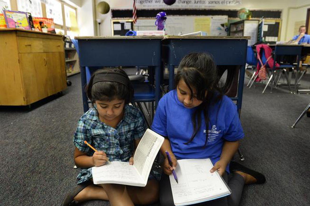 Fifth-graders Abril Magallanes, 10, left, and Julie Vazquez, 10, work together during a math lesson at McMeen Elementary School in 2014.