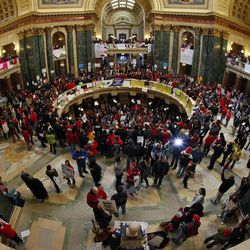 """Opponents to the governor's bill to eliminate collective bargaining rights for  state workers protest in the rotunda of the State Capitol in Madison, Wis., Saturday, Feb. 19, 2011.  A few dozen police officers stood between supporters of Republican Gov. Scott Walker on the muddy east lawn of the Capitol and the much larger group of pro-labor demonstrators who surrounded them.   The protest was peaceful as both sides exchanged chants of """"Pass the bill! Pass the bill!"""" and """"Kill the bill! Kill the bill!""""  The Wisconsin governor, elected in November""""™s GOP wave that also gave control of the state Assembly and Senate to Republicans, set off the protests earlier this week by pushing ahead with a measure that would require government workers to contribute more to their health care and pension costs and largely eliminate their collective bargaining rights."""