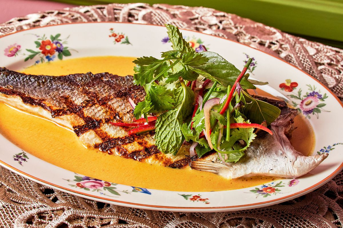 Grilled fish topped with fresh herbs on a shabby chic colorful plate.