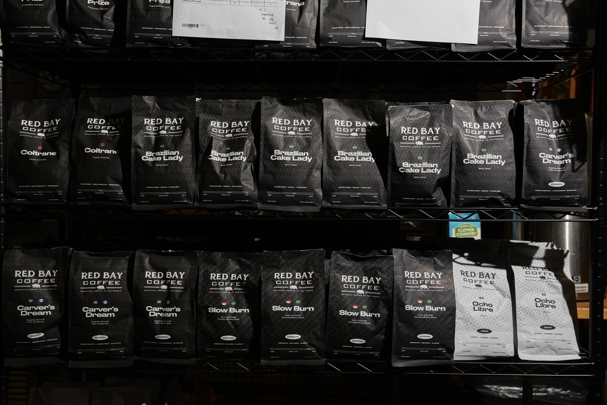 Black bags of Red Bay Coffee lined up on shelves.
