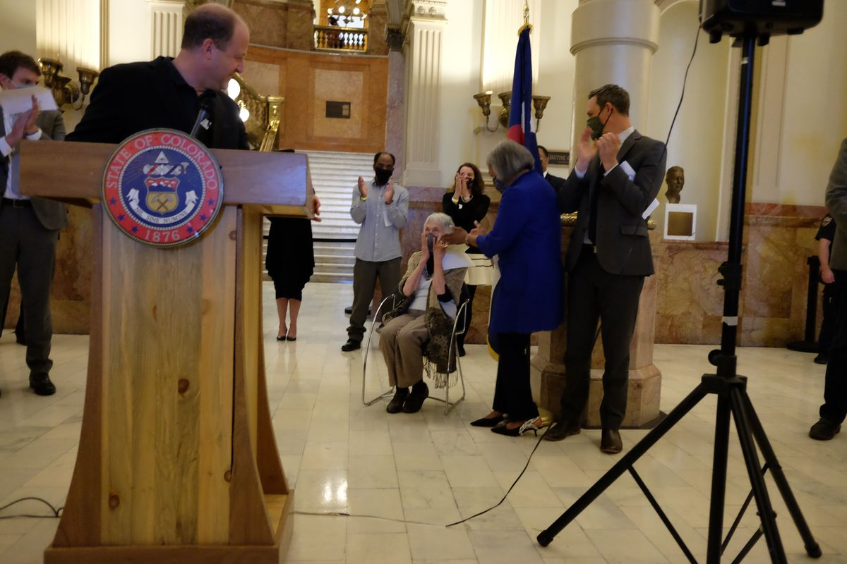 Gov. Jared Polis stands at a podium and turns to look at early childhood advocate Anna Jo Haynes, seated. She clasps her hands to her face in surprise. Lawmakers standing nearby applaud.