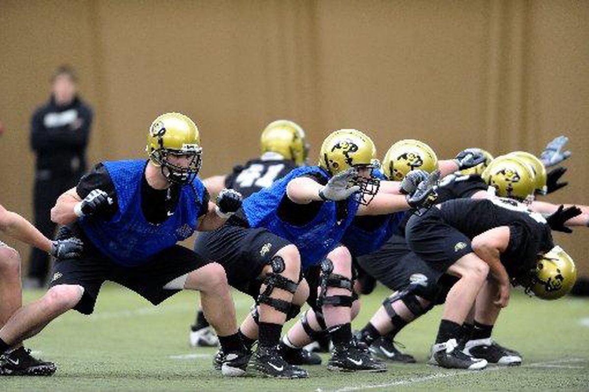 Offensive linemen practice their post-snap positions during the University of Colorado's first football practice of the season on Tuesday. Photo: Marty Caivano