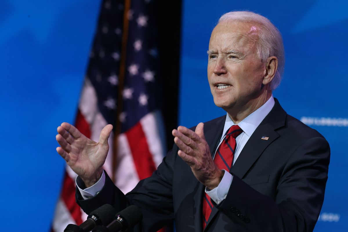 President Joe Biden speaks in front of an American flag and a blue background.