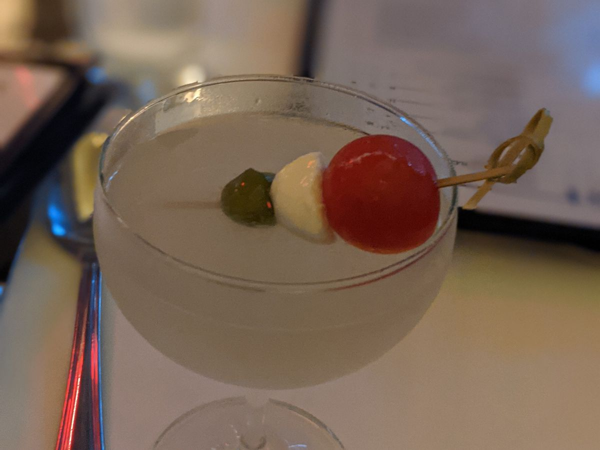 A martini with olive, mozzarella, and cherry tomato as garnish, on a table with a menu
