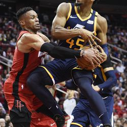 Utah Jazz guard Donovan Mitchell (45) is wrapped up by Houston Rockets guard Russell Westbrook during the second half of an NBA basketball game, Sunday, Feb. 9, 2020, in Houston.