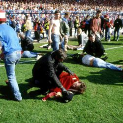 FILE - In this April 15, 1989 file photo, showing police, stewards and supporters as they tend to wounded soccer supporters on the field at Hillsborough Stadium, in Sheffield, England. 96 Liverpool fans were crushed to death in the incident at the FA Cup semi-final match Liverpool against Nottingham Forest. After a long campaign by relatives of the 96 soccer fans who were crushed to death in Britain's worst sporting disaster, some 400,000 pages of previously undisclosed papers will be released Wednesday Sept. 12, 2012, and the previously secret documents may clarify what caused the disaster and how mistakes by British authorities may have contributed to the 1989 tragedy. (AP Photo, File)