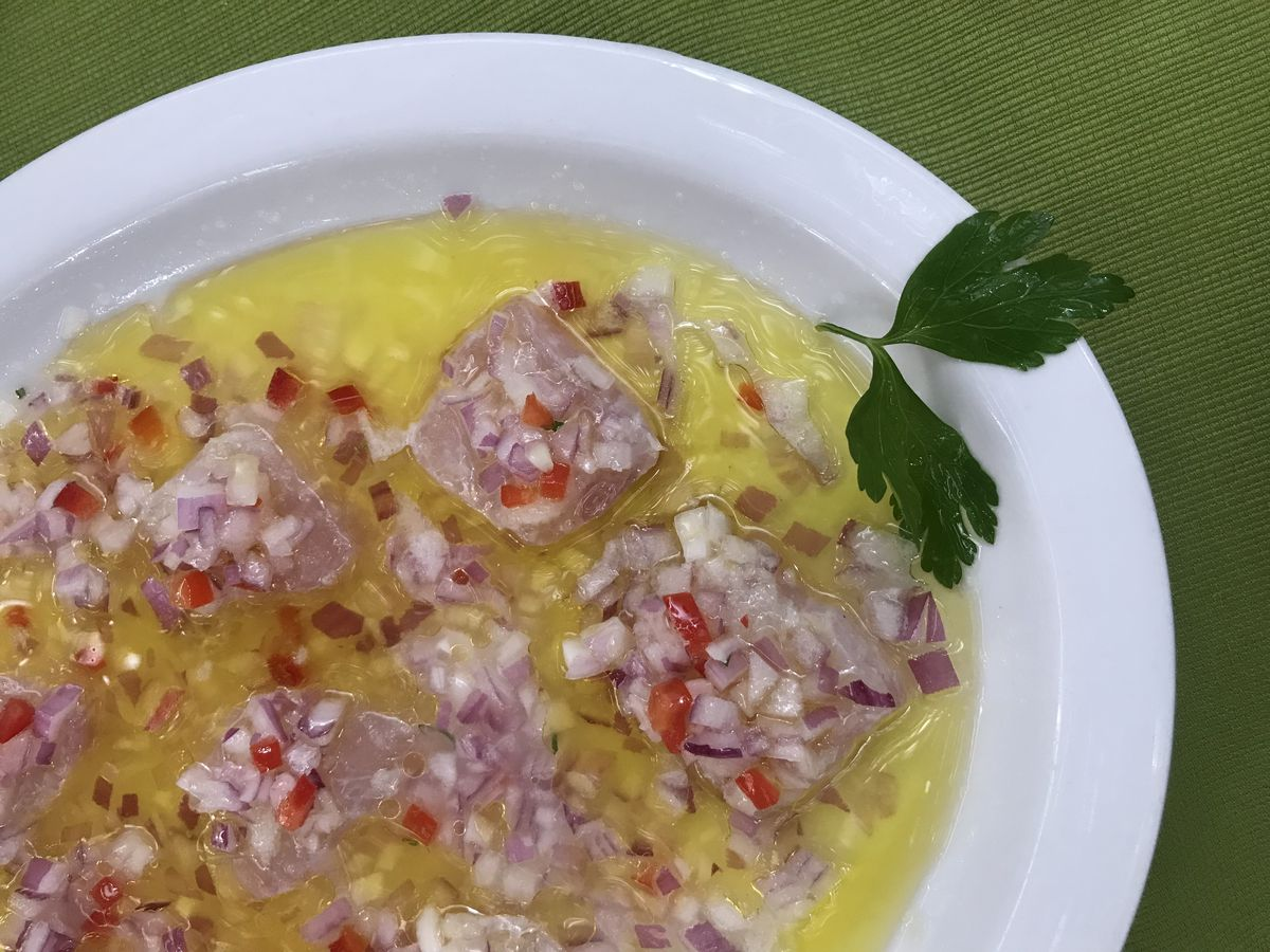 Slices of raw sole sit on a dish in a bath of olive oil, topped with minced onion and garlic, and garnished with a sprig of herbs.