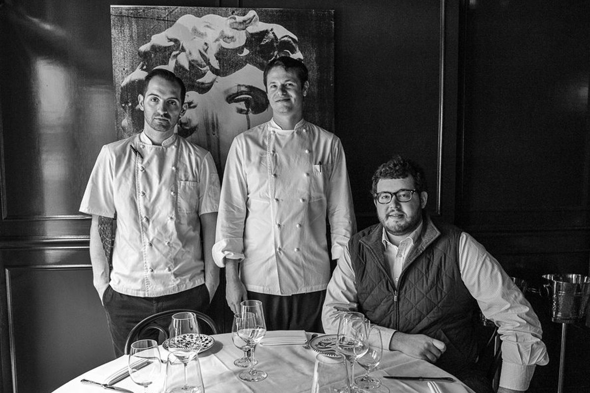 A black-and-white photo of Mario Carbone and Rich Torrisi, who are standing and wearing chef's whites, and a sitting Jeff Zalaznick, who wears a vest.