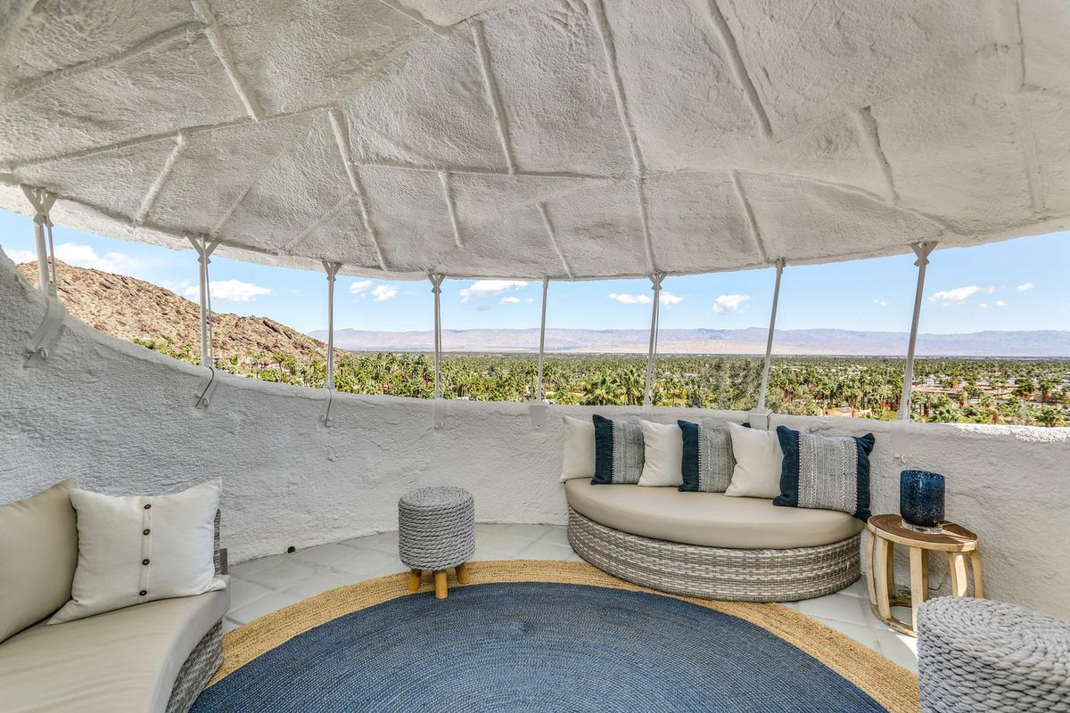 The interior of a turret-like structure with white walls, seating areas, and views of the desert.
