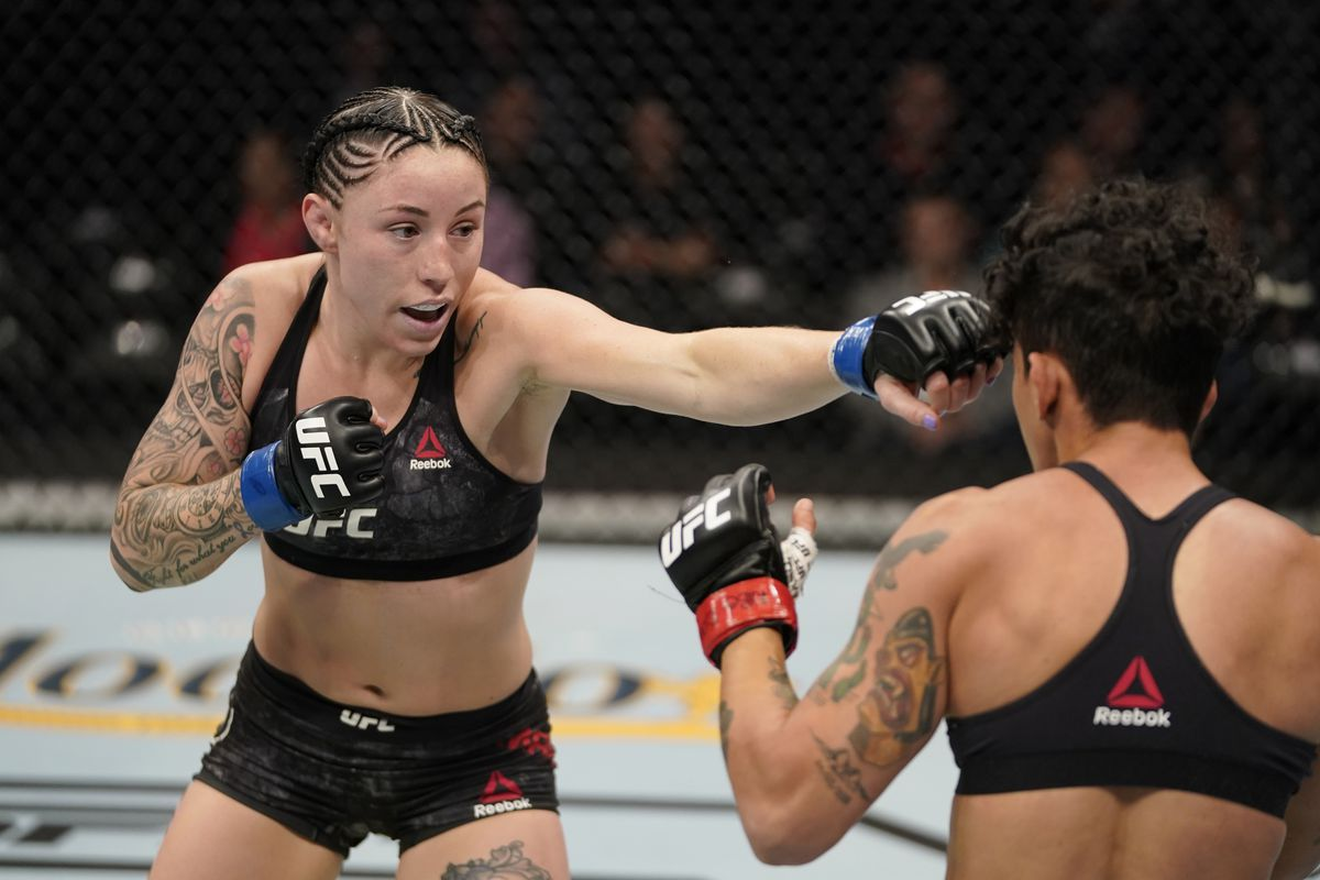 Mallory Martin punches Virna Jandiroba of Brazil in their women's strawweight bout during the UFC Fight Night event at Capital One Arena on December 07, 2019 in Washington, DC.