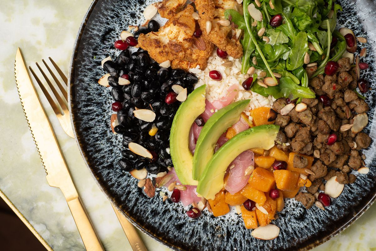 A cauliflower rice plate with beans, avocado, and Beyond meat.