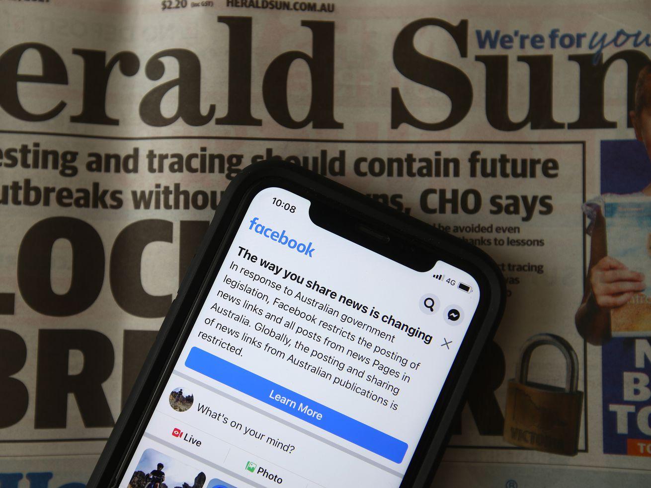 Une photo d'un téléphone avec une publication sur Facebook avec un journal australien en arrière-plan.