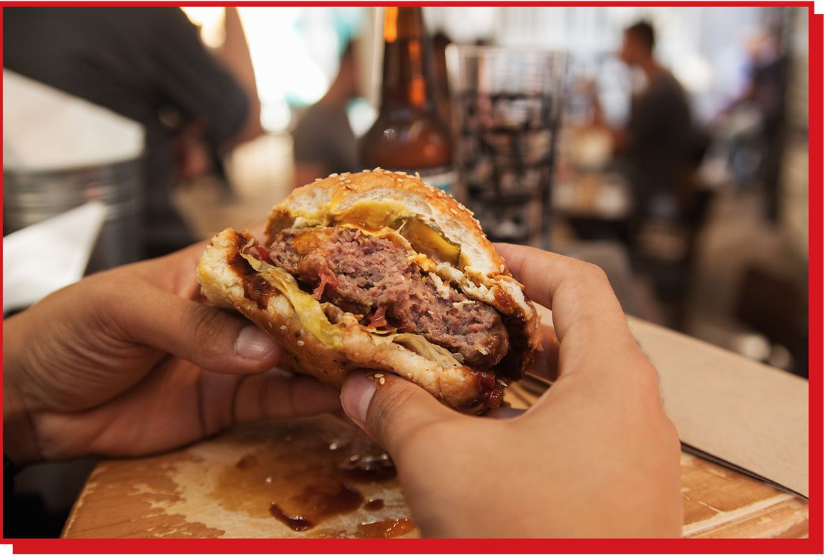 Pair of hands holds half a burger.
