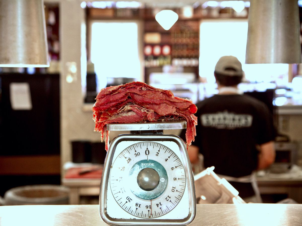 Slices of meat on an old fashioned scale, sitting on a counter in front of an open kitchen where a cook works