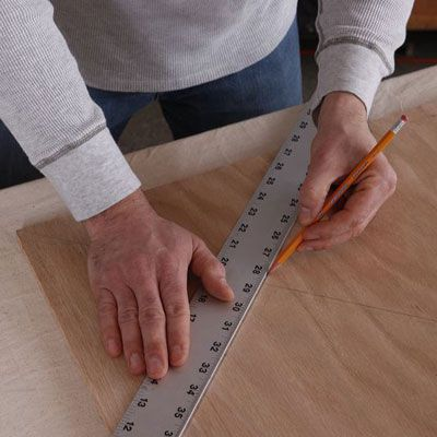Person holding a ruler on a DIY poker table and using a pencil to mark where they will make a cut.