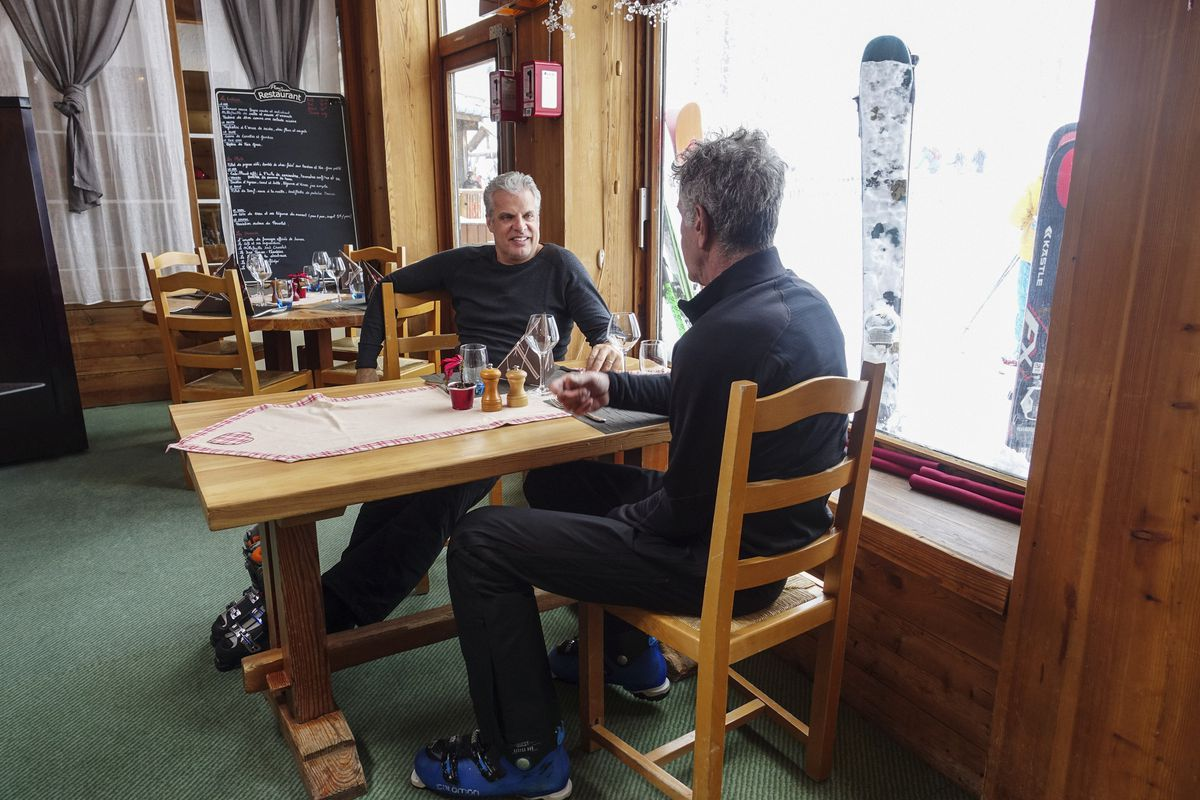 Eric Ripert and Anthony Bourdain sitting at a table during a scene from Parts Unknown.