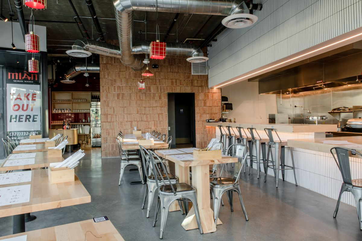 Long tables and metal chairs inside of a new restaurant set for service.