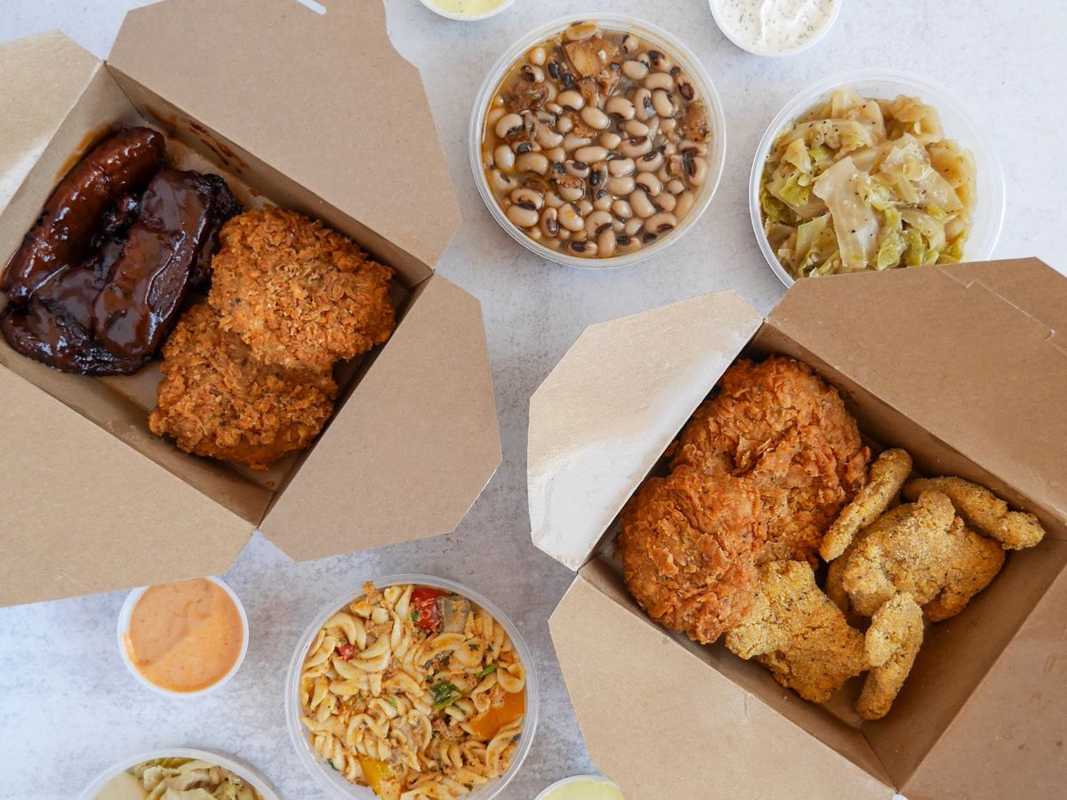 Two takeout boxes of fried and barbecue vegan meats from Dirty Lettuce, with sides of black-eyed peas, greens, and jambalaya